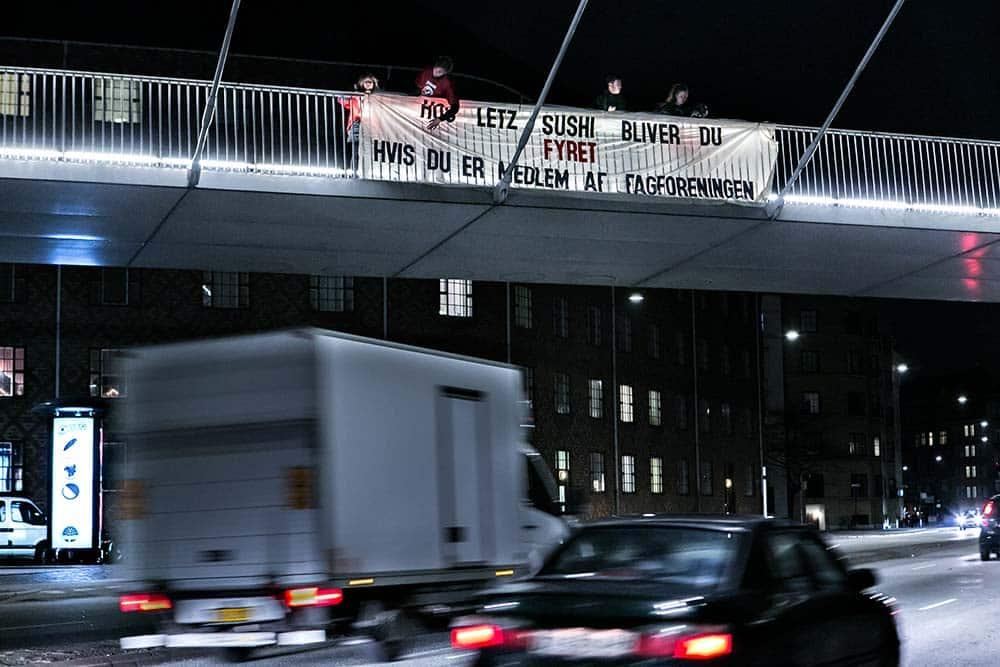 3F hænger bannere op mod restauranten Letz Sushi pga. dårlige arbejdsforhold for de ansatte.
